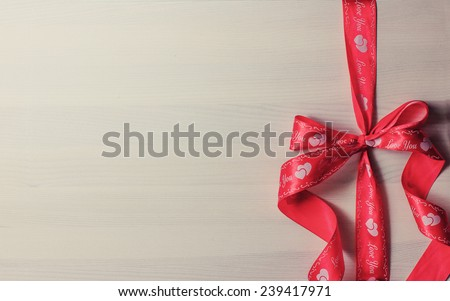 Decorative red ribbon with bow on wooden background with copyspace/ Holidays background / Valentines day background - stock photo