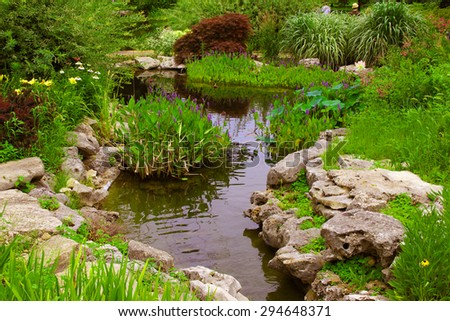 Decorative rocks near a small pond in a garden - stock photo