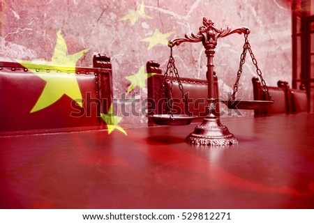 Decorative Scales of Justice on the red table with Chinese flag