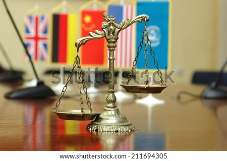 Decorative Scales of Justice with blurred National flag of different countries, concept of International Law and Order, focus on the scales - stock photo