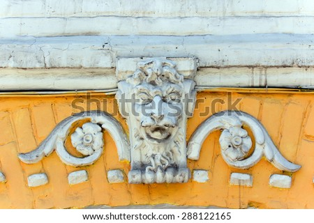 decorative sculpture in the form of a lion's head on the facade of an old building - stock photo