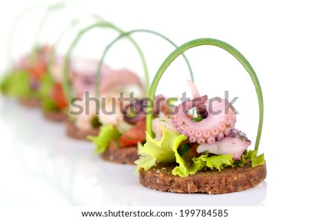 Decorative seafood salad on round slices of wholemeal bread - stock photo