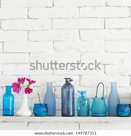 Decorative shelf on white brick wall with blue bottles on it - stock photo