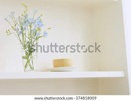 Decorative shelf on white wall with flower - stock photo