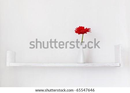 Decorative shelf on white wall with flower ina vase on it - stock photo