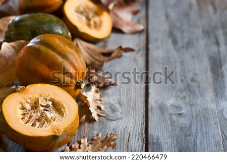 Decorative small pumpkins on fall leaves and wooden background. Selective focus. Copyspace background. - stock photo