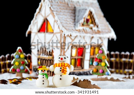 Decorative snowmen and gingerbread house with lights inside on black background. Rural Christmas night scene - stock photo