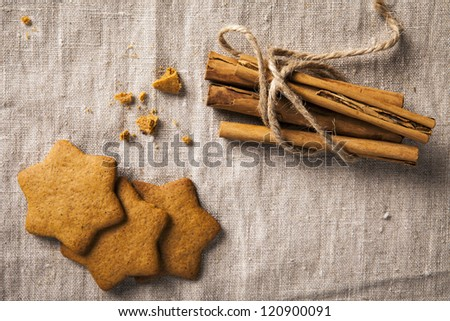 "Decorative, sparse christmas arrangement with greeting card copyspace for ""Merry Christmas""-text. Ginger bread and cinnamon sticks arranged on brown table cloth. - stock photo"