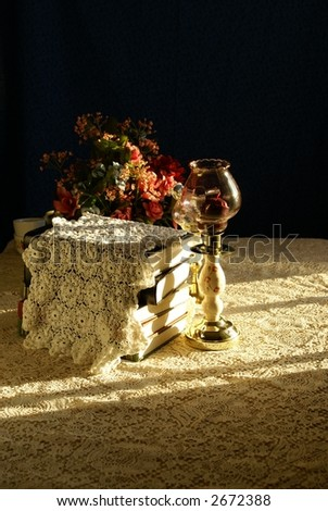 Decorative stack of hardback books draped with hand crocheted lace, laying on aged lace tablecloth. Artificial flowers and candelabra accents. Strong afternoon sidelighting for elegant flair. - stock photo