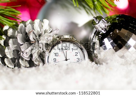 decorative star and clock on snow with christmas tree branch on blurred background - stock photo