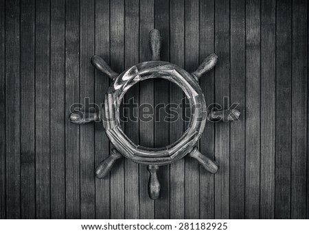Decorative steering wheel on a wooden background. Monochrome.  - stock photo