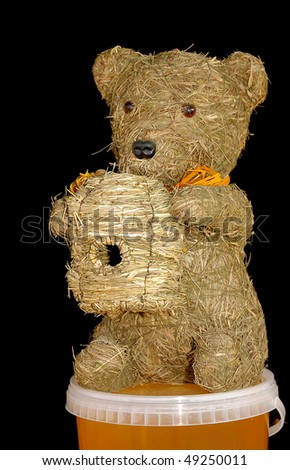 Decorative straw bear with hive sitting on honey isolated on black