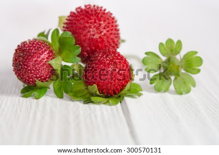 decorative strawberries on white wooden table - stock photo