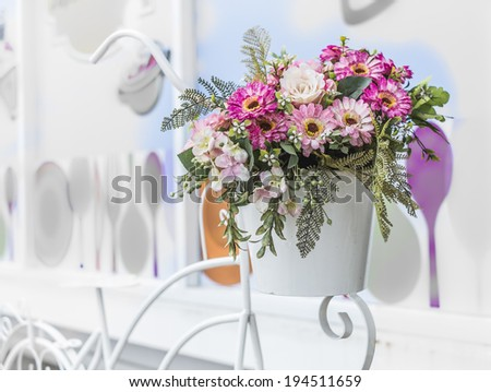 decorative the bicycle with artificial flowers on color wall background