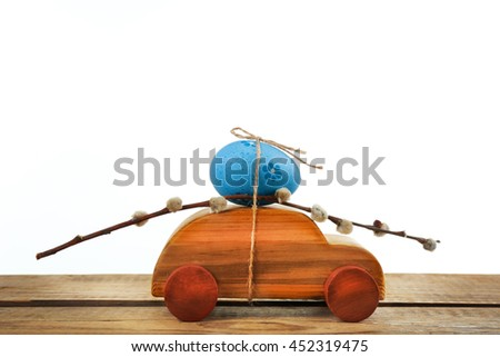 Decorative toy car with pussy willow and Easter egg, isolated on white - stock photo