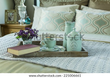 Decorative tray with book,tea set and flower on the bed - stock photo