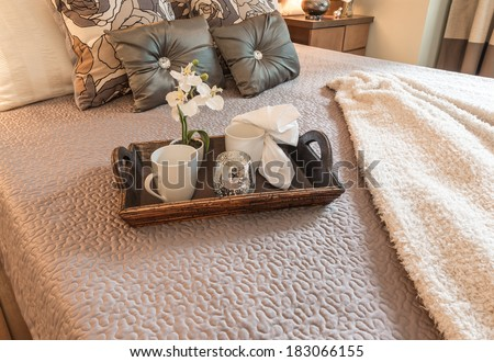 Decorative tray with tea, coffee set and flower on the bed in the luxury master bedroom. Interior design. - stock photo