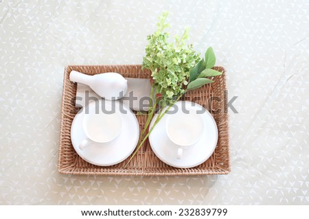 Decorative tray with tea set and flower on the bed - stock photo
