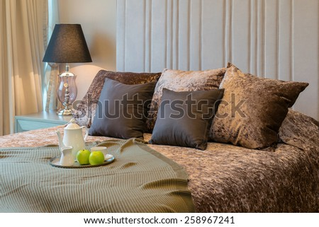 Decorative tray with tea set and green apple on the bed for breakfast. - stock photo
