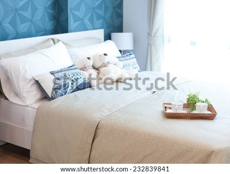 Decorative tray with teddy bear, tea set and flower on the bed - stock photo
