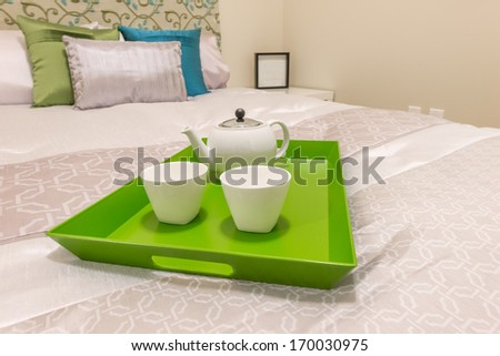 Decorative tray with the coffee set on the bed in the luxury master bedroom.  Interior design. - stock photo