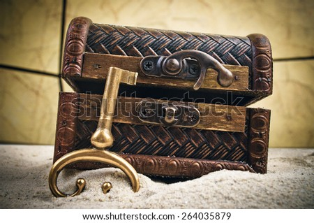 Decorative treasure chest with old metal key in the sand - stock photo