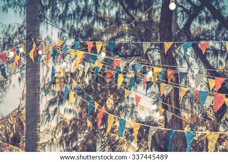 Decorative triangular flags and lamps on trees, toned - stock photo