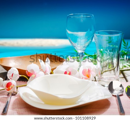 Decorative tropical table setting with stylish dinnerware and orchids overlooking the ocean at a resort restaurant - stock photo