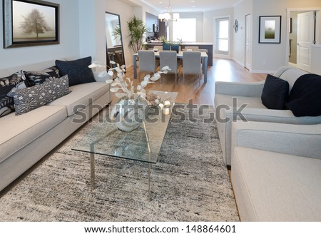 Decorative vase on the coffee table in the living room with the dinner, lunch table at the back. Interior design. - stock photo