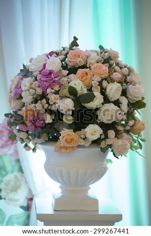 Decorative wedding bunch of fresh beautiful flowers of roses and peony white pink violet purple yellow lilac and orange colours in big vase on blue curtain background, vertical picture
