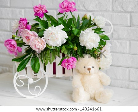Decorative wheelbarrow with white and pink peonies in it - stock photo