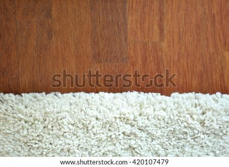 Decorative white fur carpet on wood floor background - stock photo