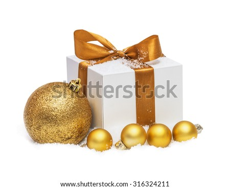 Decorative white gift box with a large gold bow and sphere standing in fresh snow - stock photo