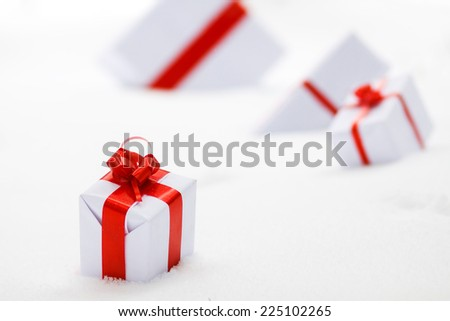 Decorative white gift boxes with a red bow standing in fresh snow - stock photo