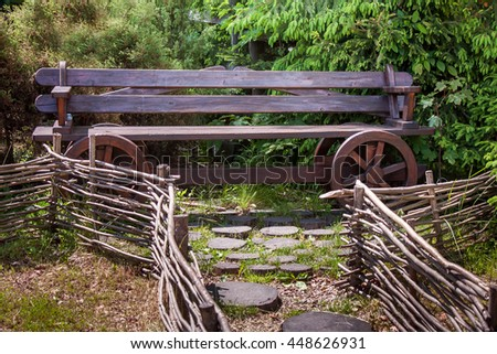 Decorative wooden bench and wicker fence in the garden - stock photo