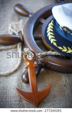 Decorative wooden ship anchored at the helm on the table - stock photo
