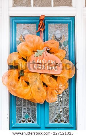 Decorative wreath on a front door - stock photo