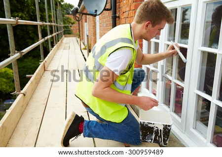 Decorator On Scaffolding Painting Exterior House Windows - stock photo