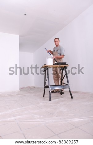 Decorator painting a room white - stock photo