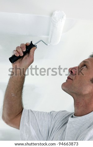 Decorator repainting ceiling - stock photo