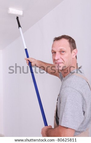 Decorator using a long roller to paint a ceiling - stock photo