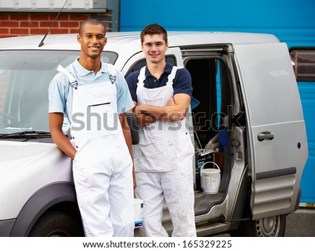 Decorators Wearing Overalls Standing Next To Van - stock photo