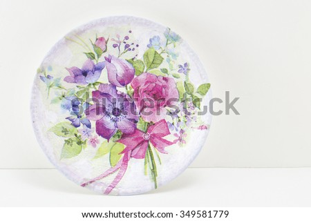 Decoupage decorated plate with flower pattern against white wooden background