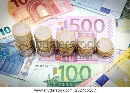 Decreasing stacks of euro coins on euro banknotes - stock photo