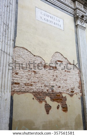 Decrepit wall with red brick and yellow paint, Venice, Italy - stock photo