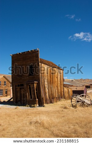 Decrepit wooden building seems about to fall down anytime, Bodie California - stock photo