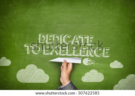 Dedicate to excellence concept on green blackboard with businessman hand holding paper plane - stock photo