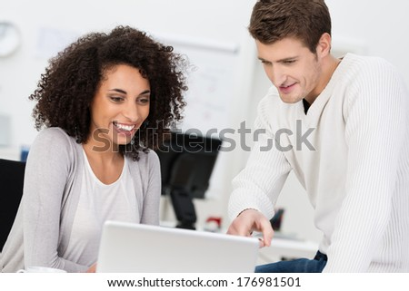 Dedicated business partners having a meeting sitting at a table in the office with an attractive young African American woman sharing information with a handsome male colleague - stock photo