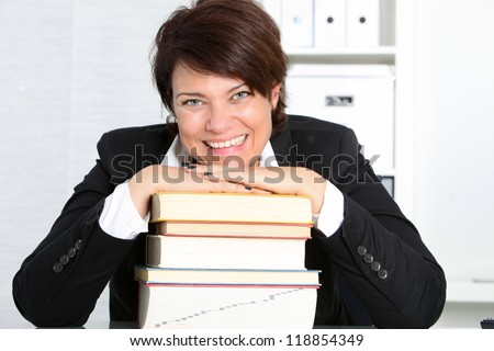 Dedicated hardworking professional woman sitting at her desk in her office with her head resting on a high stack of books smiling at the camera - stock photo