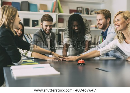 Dedication and teamwork lead to success - colleagues putting their hands together to represent unity - stock photo